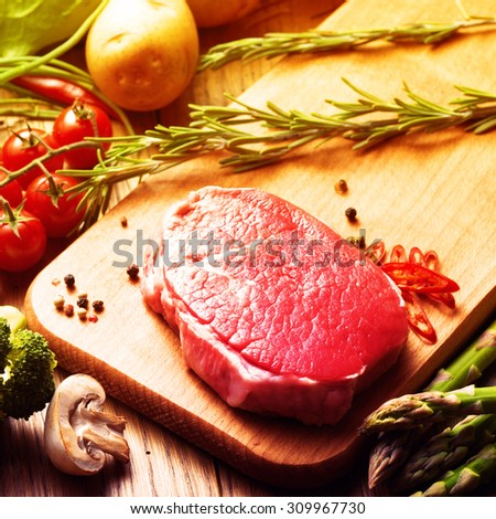 Raw Steak with green asparagus on wooden board. Filtered image: warm cross processed vintage effect. - stock photo