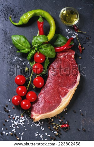 Raw steak with vegetables over black stone background. See series - stock photo