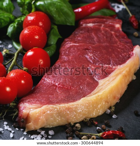 Raw steak with vegetables over black stone background. Square image with selective focus - stock photo