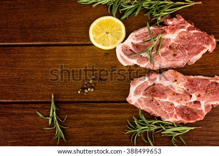 Raw steaks with lemon and rosemary on wooden background