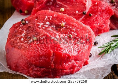 raw steaks with rosemary, sea salt and pepper on wooden background - stock photo