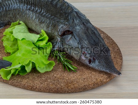 Raw strugeon on the wooden background with salad leaves and rosemary