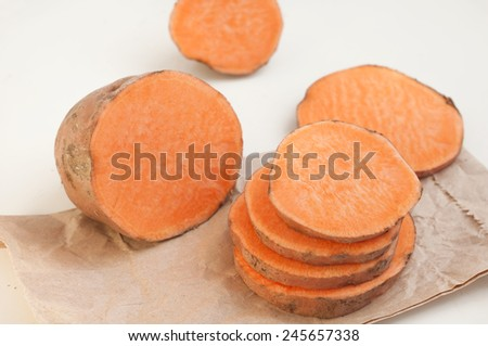 Raw sweet potato on paper package. White background