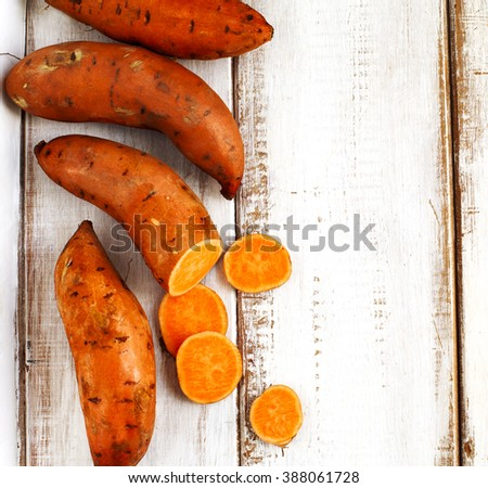 Raw sweet potatoes on wooden background - stock photo