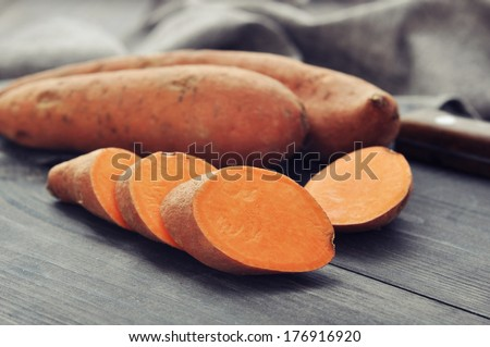 Raw sweet potatoes on wooden background closeup - stock photo