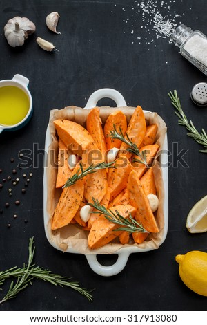 Raw sweet potatoes prepared to bake in white ceramic roasting dish. Olive oil, lemon, salt, pepper, garlic and rosemary around. Black chalkboard as background. Kitchen worktop scenery from above. - stock photo