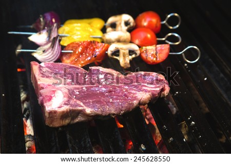 Raw T-bone steak on the barbecue grill with vegetable spears in the background - stock photo