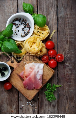 Raw tagliatelle with prosciutto ham, fresh herbs and tomatoes, Italian pasta ingredients - stock photo