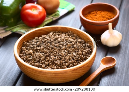 Raw textured vegetable or soy protein, also soy meat in wooden bowl, vegetables, paprika powder in the back. Photographed with natural light (Selective Focus, Focus one third into the soy meat)  - stock photo