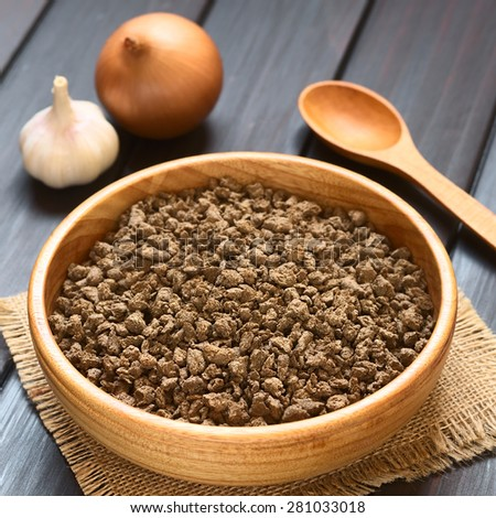 Raw textured vegetable or soy protein called also soy meat in wood bowl, onion, garlic, spoon in back, photographed on dark wood with natural light (Selective Focus, Focus one third into soy meat)  - stock photo