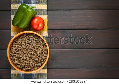 Raw textured vegetable or soy protein, called also soy meat in wooden bowl with bell pepper and tomato on kitchen towel. Photographed overhead on dark wood with natural light.  - stock photo