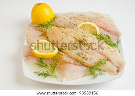 Raw tilapia fillets marinated in lemon juice - stock photo