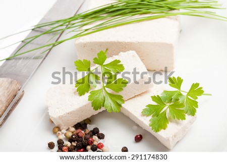 raw tofu slices decorated with parsley and chives on white plate with salt, pepper and old knife - stock photo