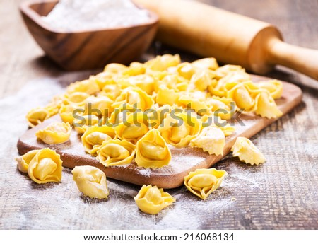 raw tortellini with flour on wooden table - stock photo