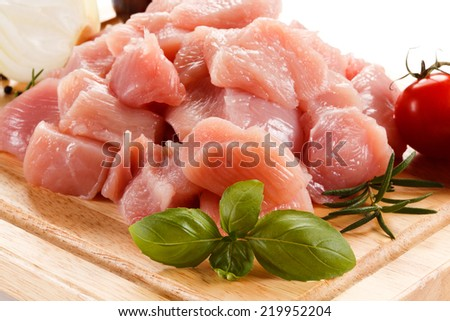 Raw tourkey meat on cutting board on white background - stock photo