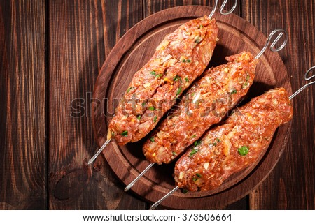 Raw traditional shish kebab on wooden cutting board