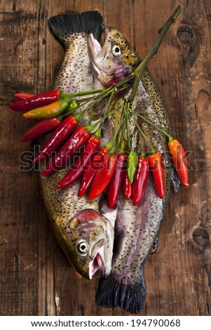 raw trouts with chilly peppers - stock photo