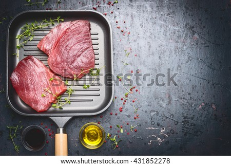 Raw Tuna Steak in grill frying pan with herbs and oil on dark aged vintage background, top view, place for text - stock photo