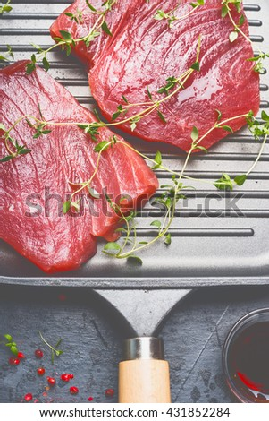 Raw Tuna Steaks in grill frying pan with herbs , top view, close up - stock photo