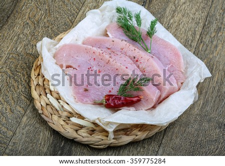 Raw turkey steak with dill and red pepper ready for cooking