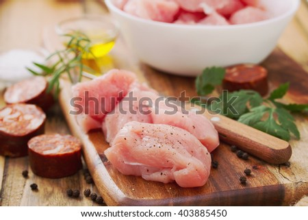 raw turkey with black pepper on brown wooden board and smoked sausage - stock photo