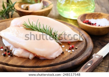 Raw uncooked chicken breast with fresh rosemary sprig and pink pepper corns and kosher salt on rustic wooden cutting board - stock photo