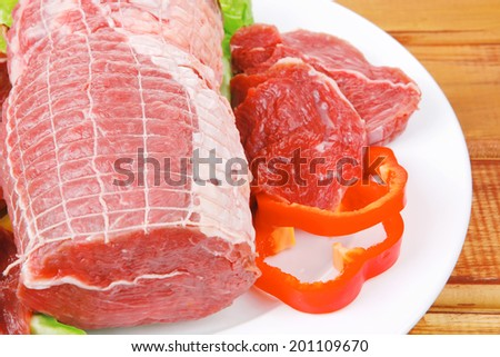 raw uncooked meat on wooden table with vegetables - stock photo
