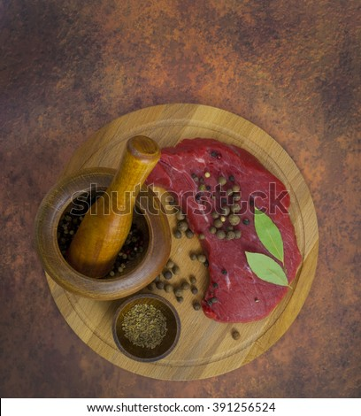 Raw uncooked meat  with fresh herbs, vegetables and spices on rustic wooden background - stock photo