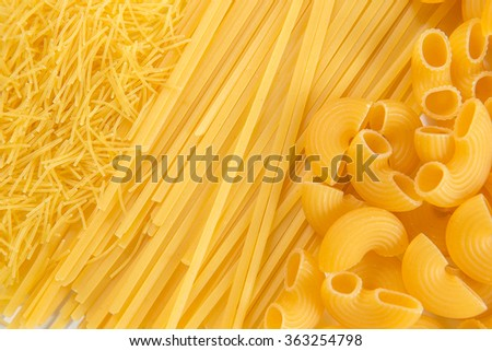 Raw uncooked pasta in bowl over white background - stock photo