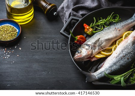 Raw uncooked seabass fish with herbs and spices in cast iron cooking pan on black wooden background. Copy space, selective focus - stock photo