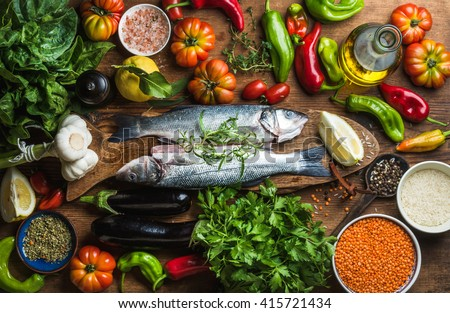 Raw uncooked seabass fish with vegetables, grains, herbs and spices on chopping board over rustic wooden background, top view - stock photo