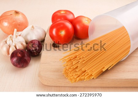 Raw uncooked spaghetti in plastic container with cooking ingredients - stock photo