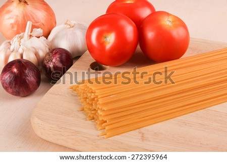 Raw uncooked spaghetti with cooking ingredients - stock photo
