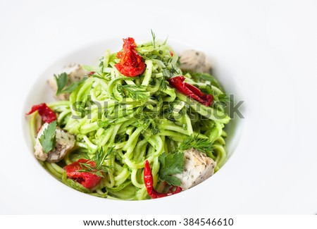Raw vegan Cucumber noodles with red capsicum and cheese from nut at white plate in the restaurant - stock photo