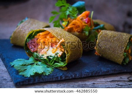 Raw vegan zucchini wraps with carrots, dairy-free sauce, cilantro, greens, lettuce and tomatoes on a slate plate against a wooden background. Vegetarian food.