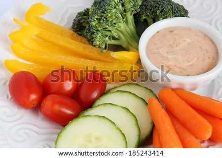 Raw vegetables � broccoli, pepper, tomato, cucumber, carrot � on white plate with dip - stock photo