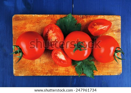 raw vegetables : fresh raw ripe tomatoes on cutting board over blue table - stock photo