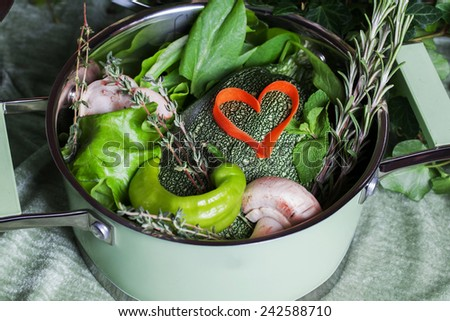 raw vegetables in a saucepan and heart carrots, love for cooking - stock photo