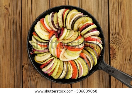 Raw vegetables layed for ratatouille made of eggplants, squash, tomatoes and onions in black cast iron pan on wooden table - stock photo