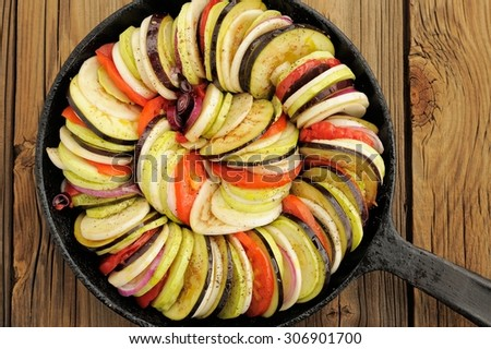 Raw vegetables layed for ratatouille made of eggplants, squash, tomatoes and onions in black cast iron pan on wooden table above - stock photo