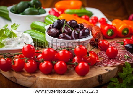 Raw vegetables, yogurt dip and antipasti. - stock photo