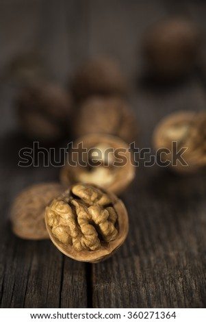 Raw walnuts with shells on wood table - stock photo