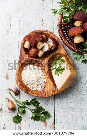 Raw white rice in olive wood bowl with ingredients for risotto with wild mushrooms - stock photo
