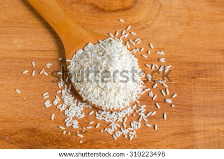 Raw white rice in spoon on wooden background,Selective focus - stock photo