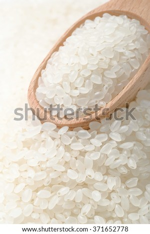 raw white rice in wooden spoon