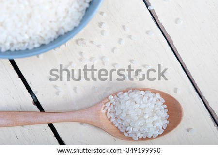 raw white rice on wood spoon and blue bowl extreme close up  - stock photo