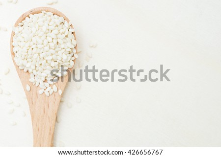 raw white sesame seeds in wooden spoon.white sesame seeds