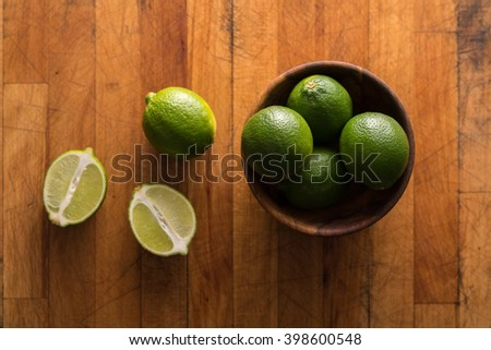 Raw whole and sliced  limes in bowl on rustic wood - stock photo