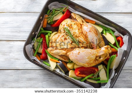 raw whole chicken with colorful pieces of peppers, potatoes. eggplant, green beans rosemary leaves in the baking dish, preparing for roast in the oven for the festive dinner, top view - stock photo