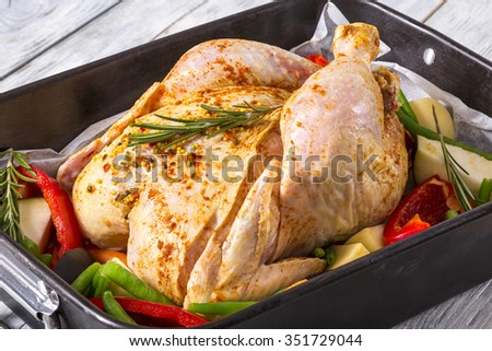 raw whole chicken with colorful pieces of peppers, potatoes. eggplant, green beans rosemary leaves in the baking dish, preparing for roast in the oven for the festive dinner, top view, close-up - stock photo